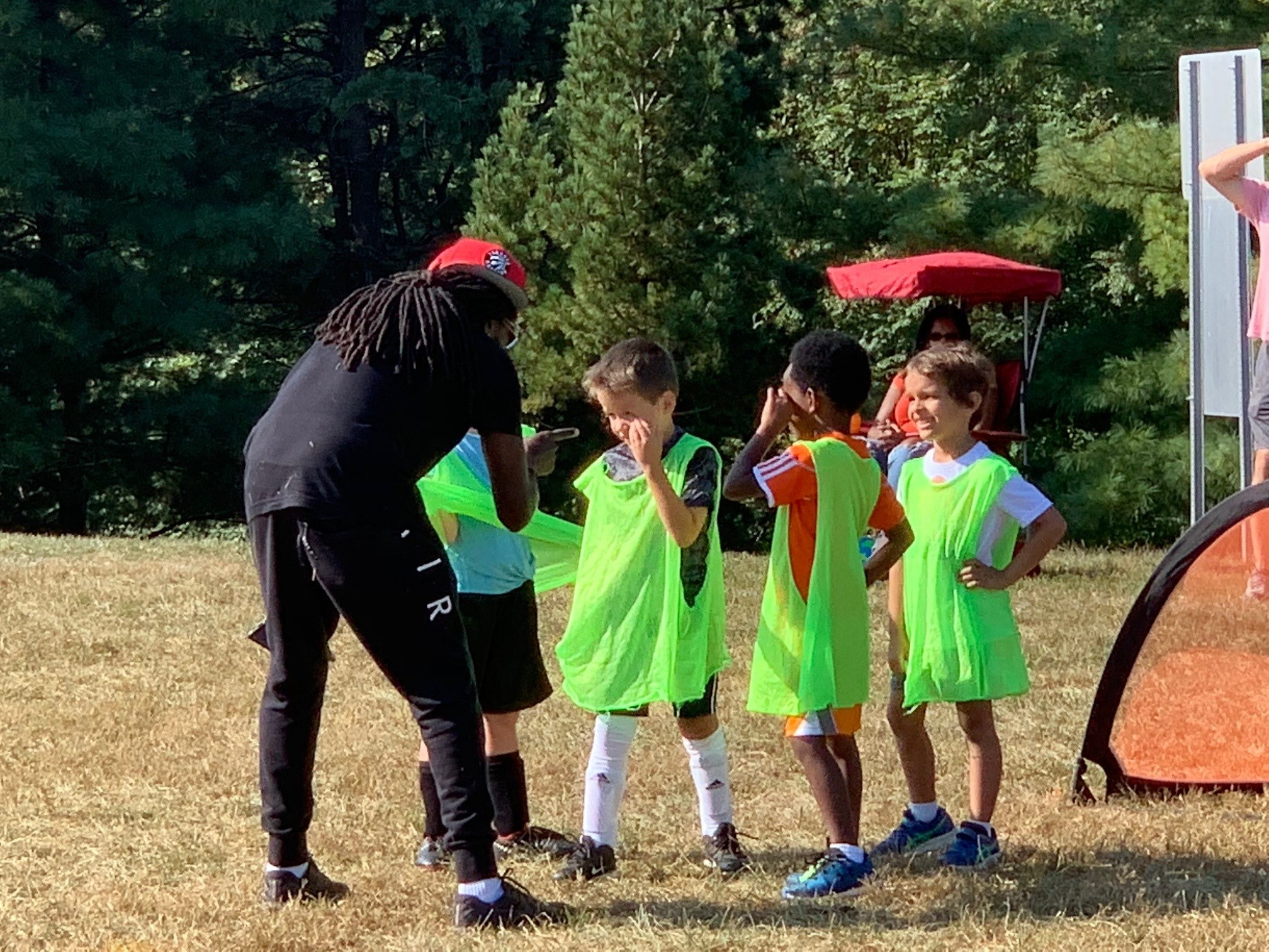 An image of a coach encouraging 4 5-year-old players wearing green training vests